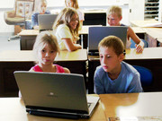 Children share a laptop in a computer lab.