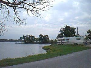 An RV parked near a body of water.